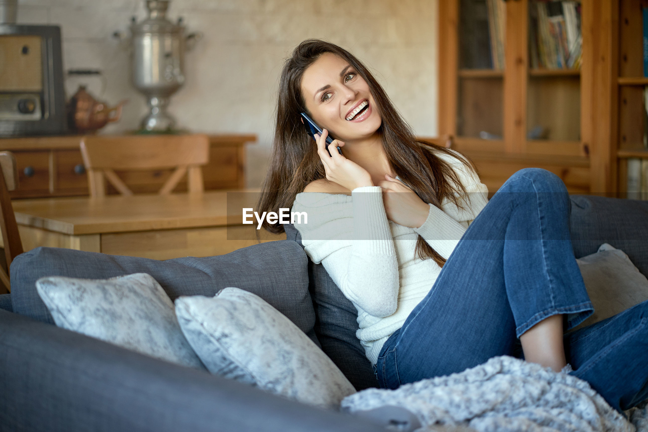 Cheerful woman talking on mobile phone while sitting on sofa at home