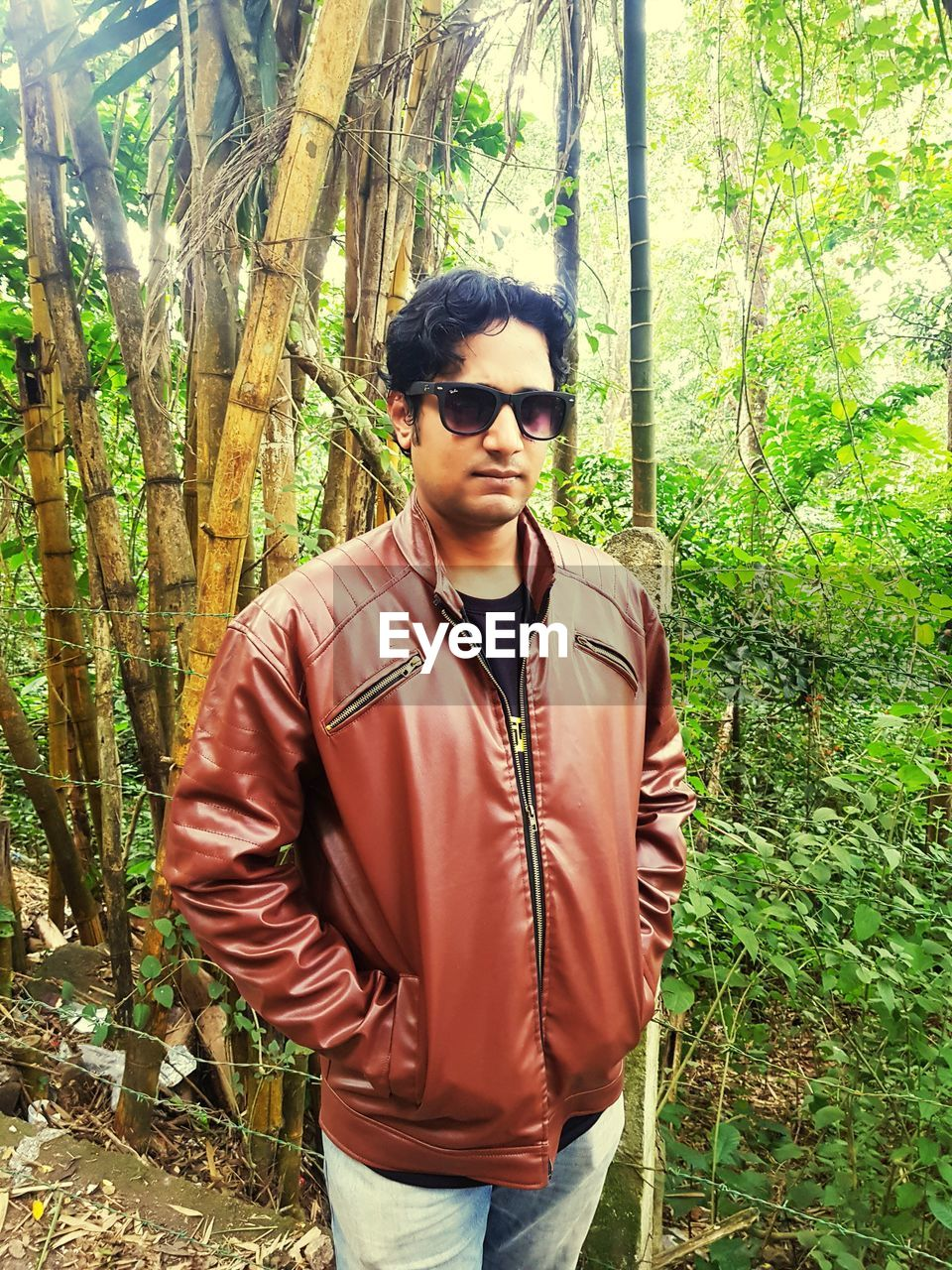 standing, glasses, sunglasses, tree, fashion, young men, one person, real people, plant, young adult, lifestyles, front view, leisure activity, casual clothing, land, forest, day, clothing, nature, outdoors