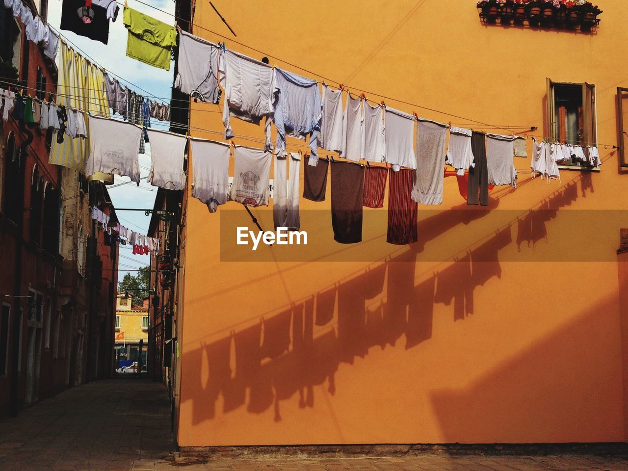 Low Angle View Of Clothes Drying On Clothesline Against Buildings