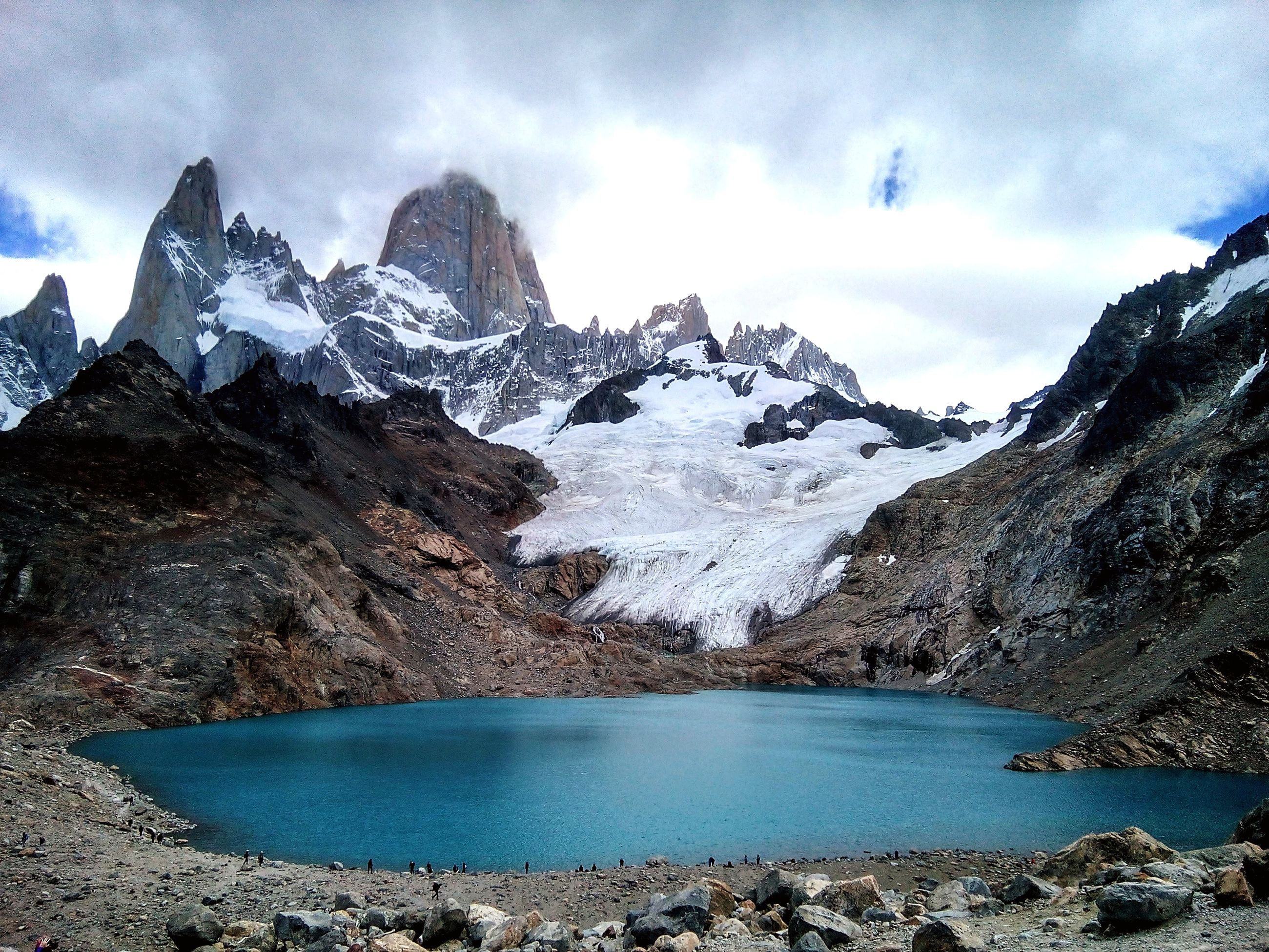 Scenic view of lake by snowcapped mountains against cloudy sky