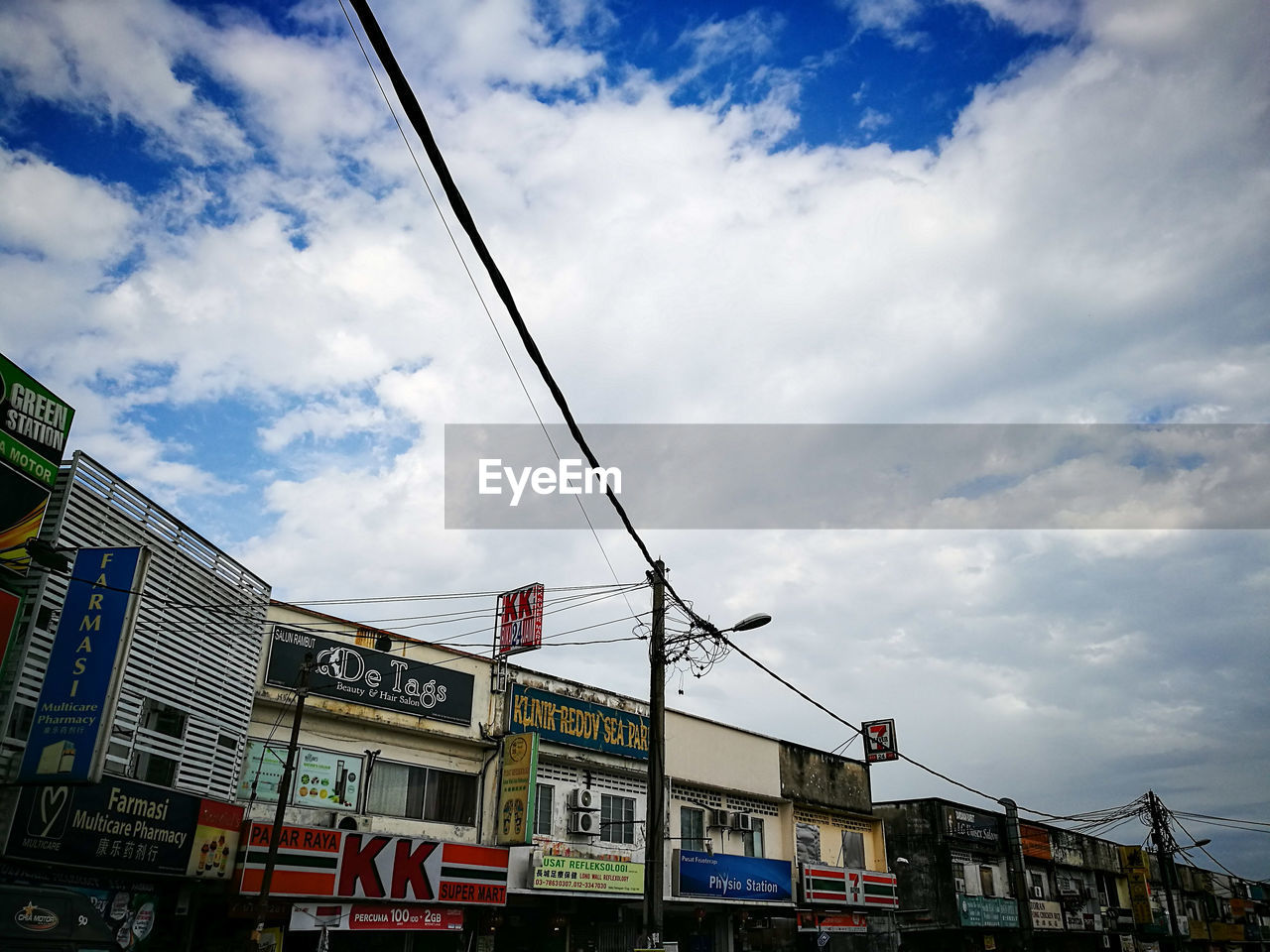 text, communication, sky, cloud - sky, low angle view, architecture, day, outdoors, built structure, building exterior, no people, road sign