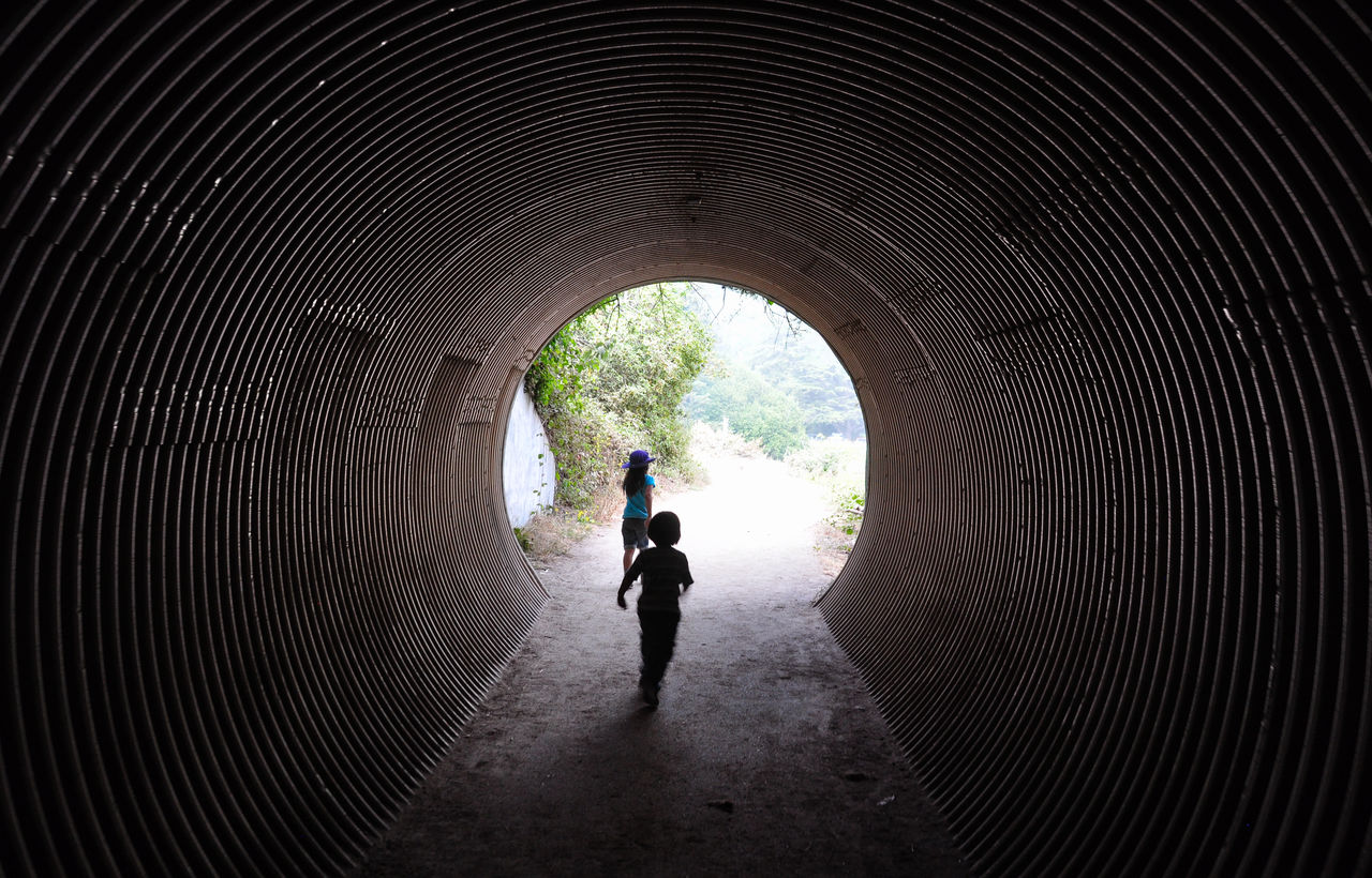 Rear View Of Sisters Running In Tunnel