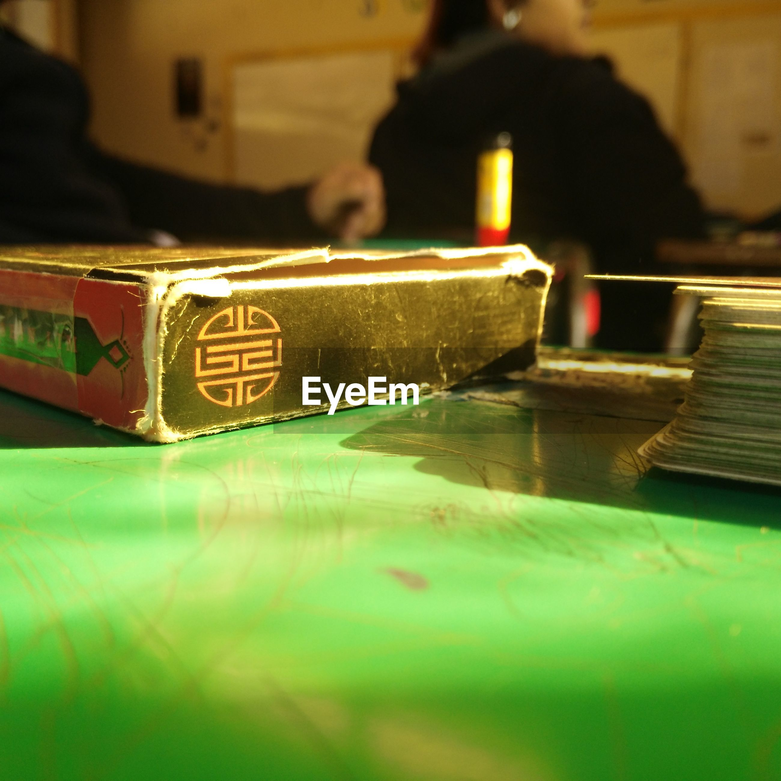 indoors, selective focus, close-up, focus on foreground, text, arts culture and entertainment, western script, communication, technology, table, reflection, illuminated, music, night, incidental people, still life, part of, surface level, men