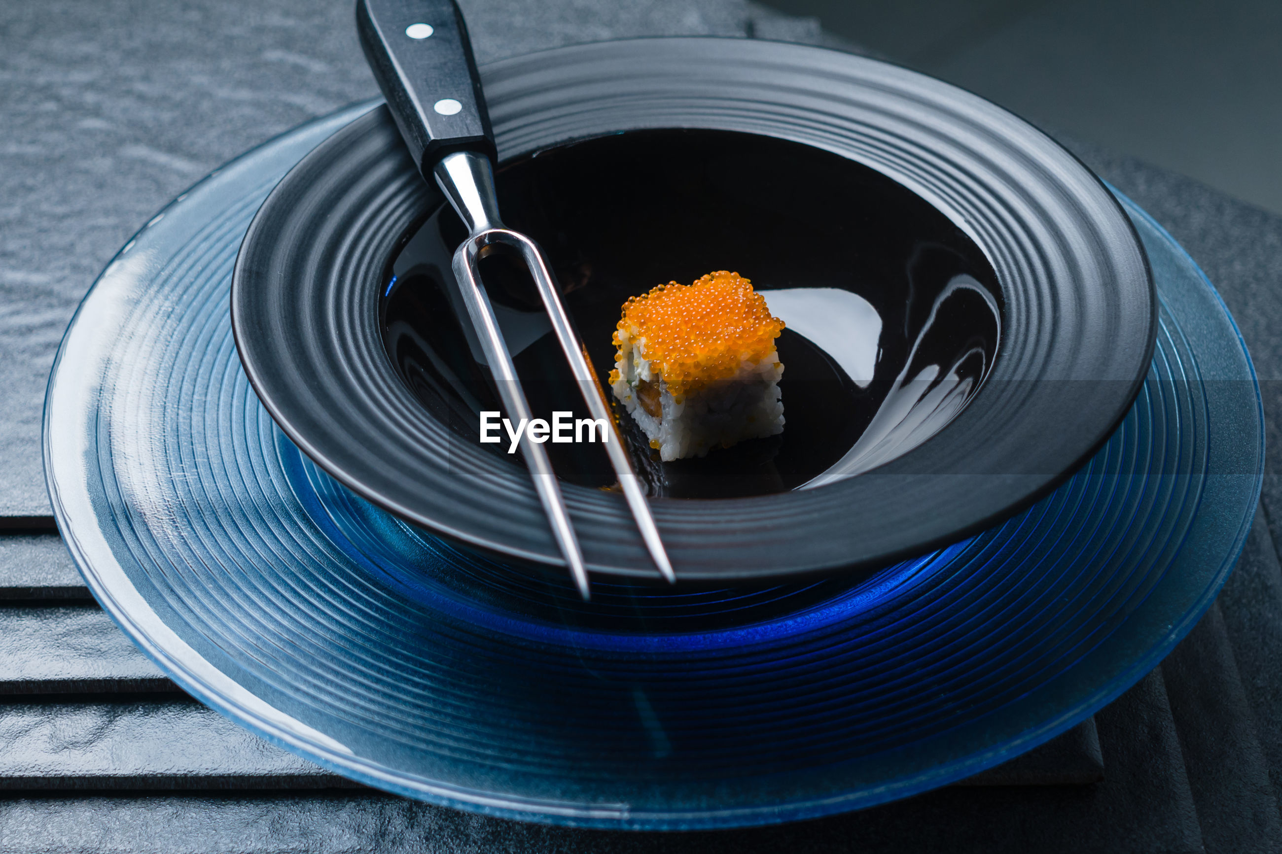 High angle view of  sushi and stainless fork in black bowl