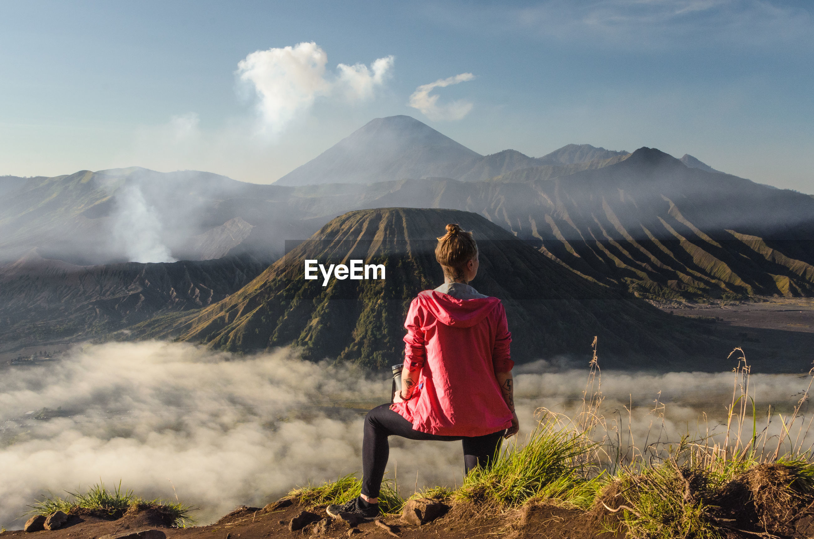 Rear view of woman standing against volcanic crater