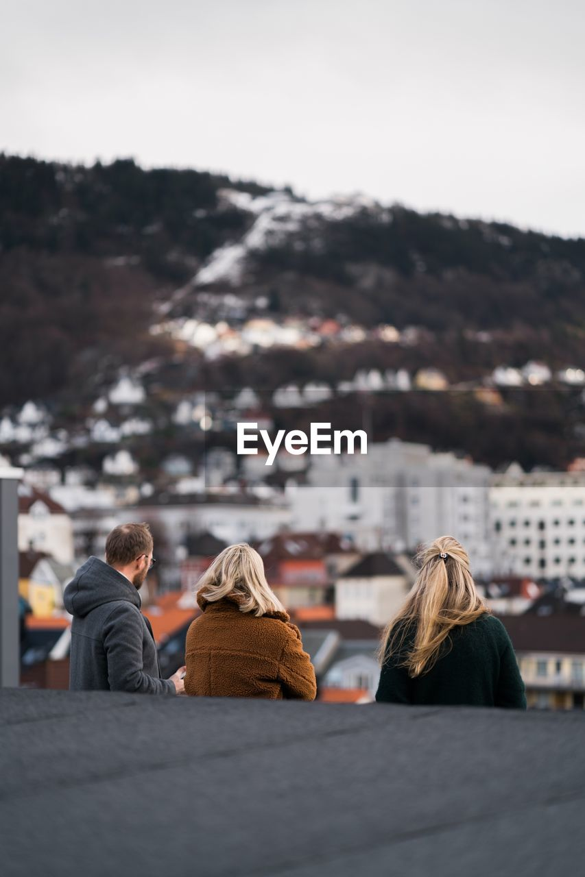 rear view, adult, architecture, city, built structure, building exterior, real people, women, group of people, lifestyles, men, togetherness, people, nature, leisure activity, focus on foreground, sky, sitting, outdoors, warm clothing, cityscape, couple - relationship