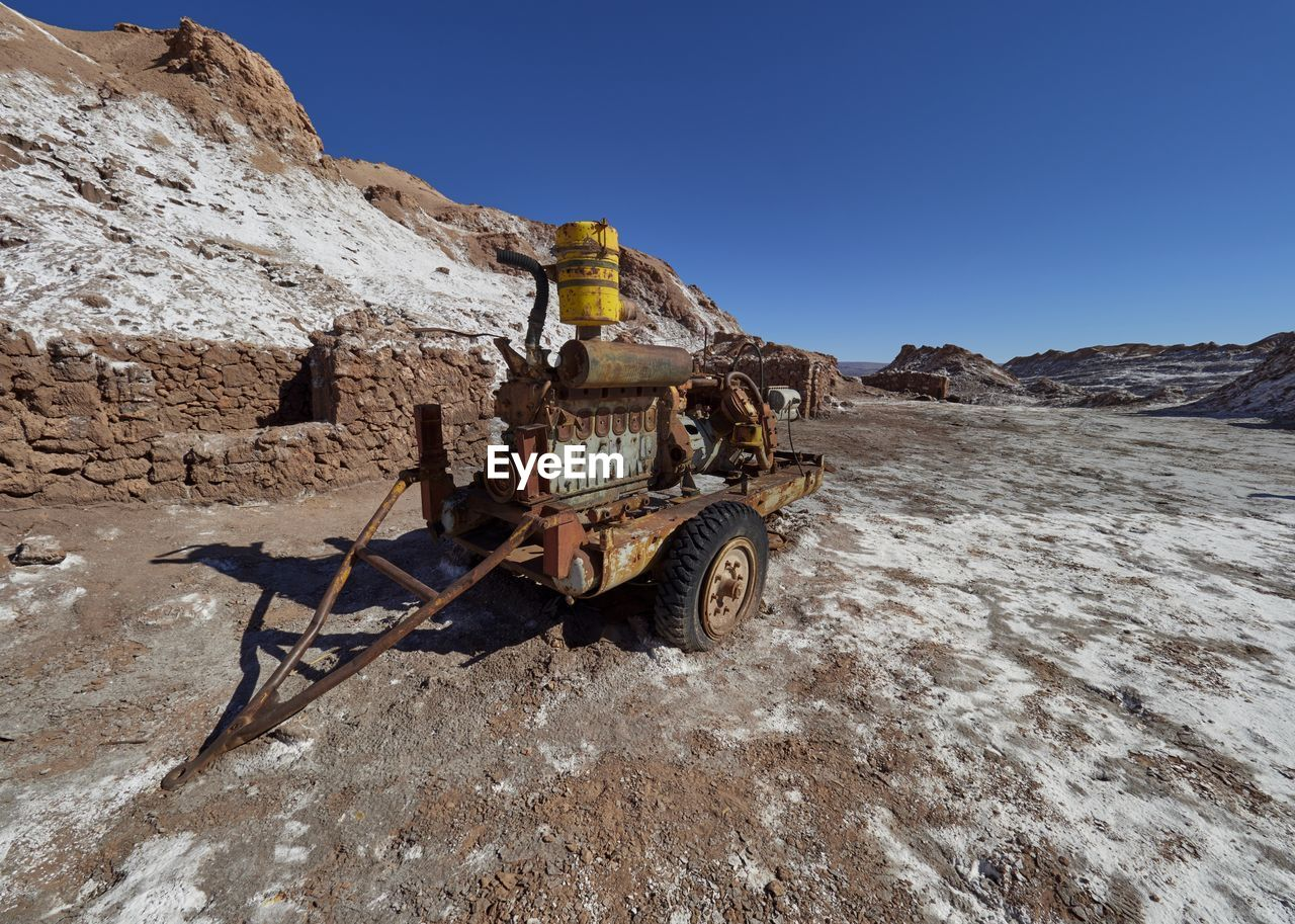 VIEW OF ABANDONED VEHICLE ON MOUNTAIN AGAINST CLEAR SKY