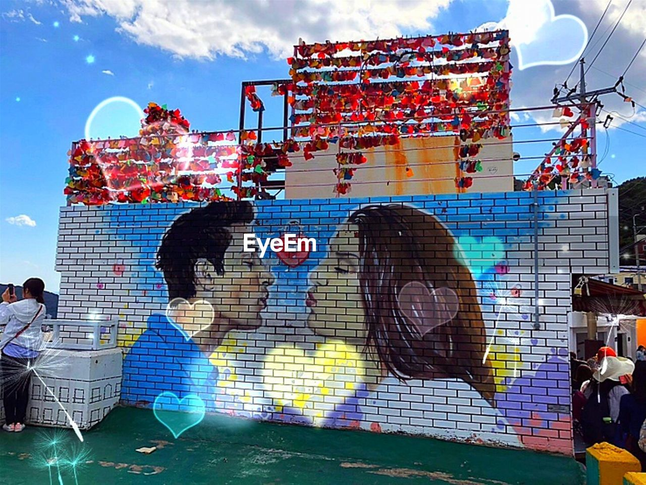 architecture, multi colored, building exterior, group of people, built structure, sky, cloud - sky, real people, day, nature, art and craft, sunlight, men, outdoors, graffiti, city, creativity, incidental people, representation, women