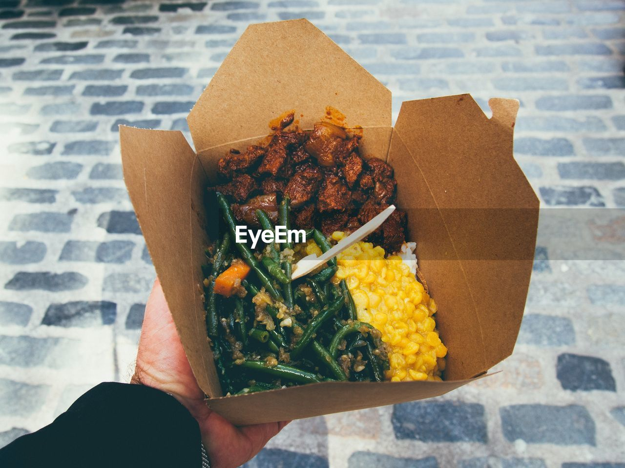Cropped Image Of Hand Holding Lunch In Box On Street