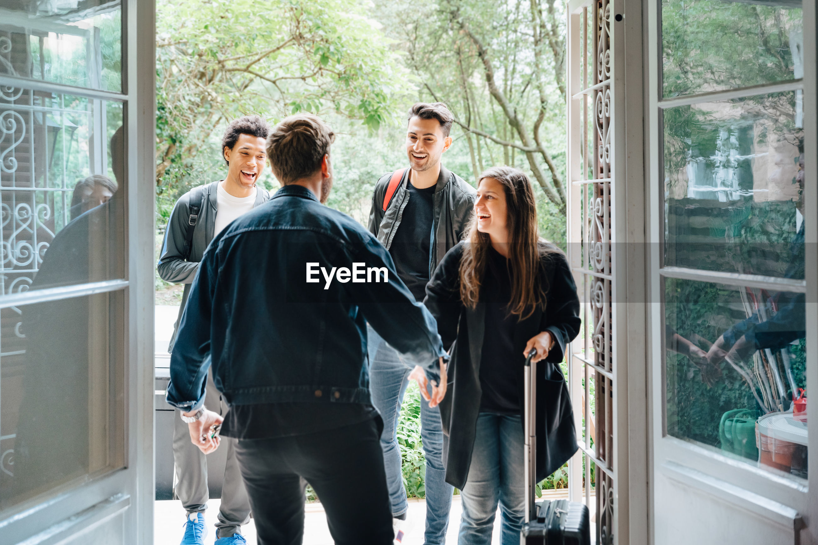 PEOPLE STANDING BY WINDOW WITH TEXT