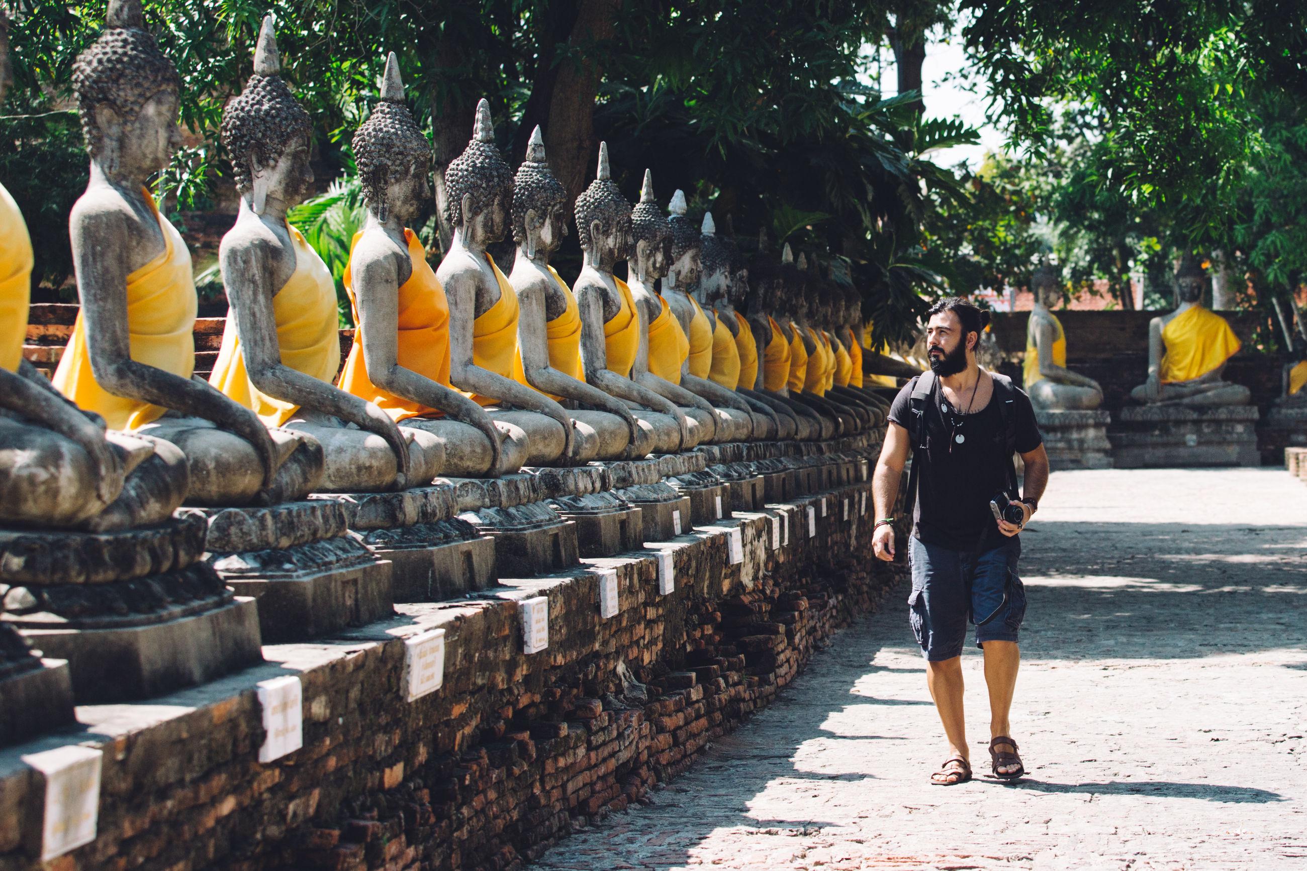 Full length of man walking by buddha statues