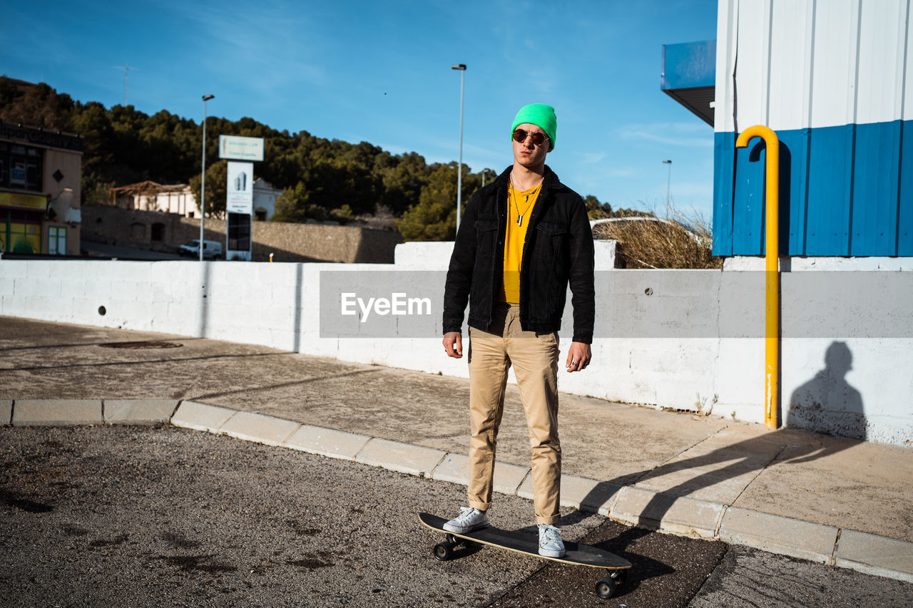 Full length of young man standing on skateboard against built structure