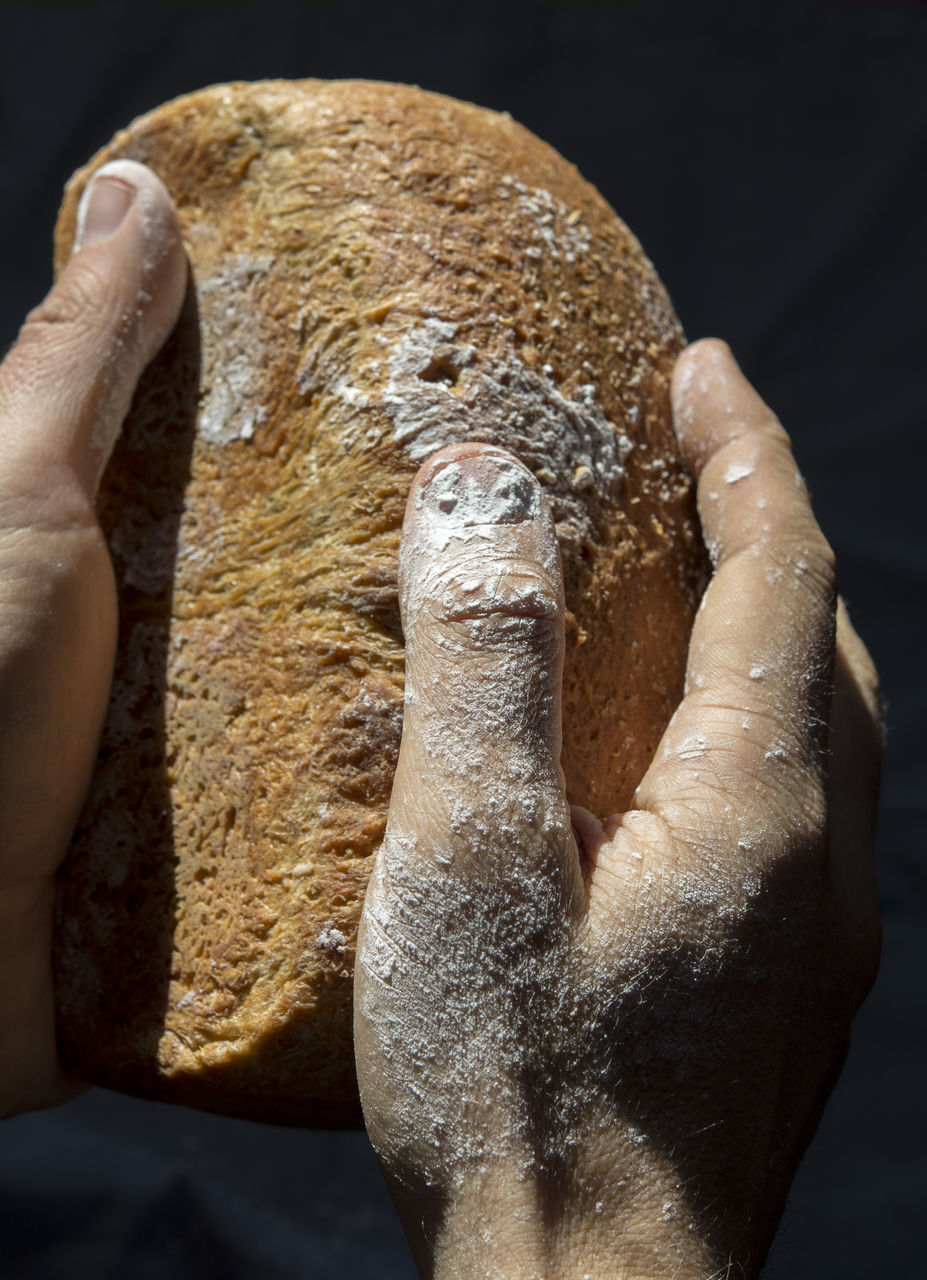 Cropped Hand Holding Bread Against Black Background