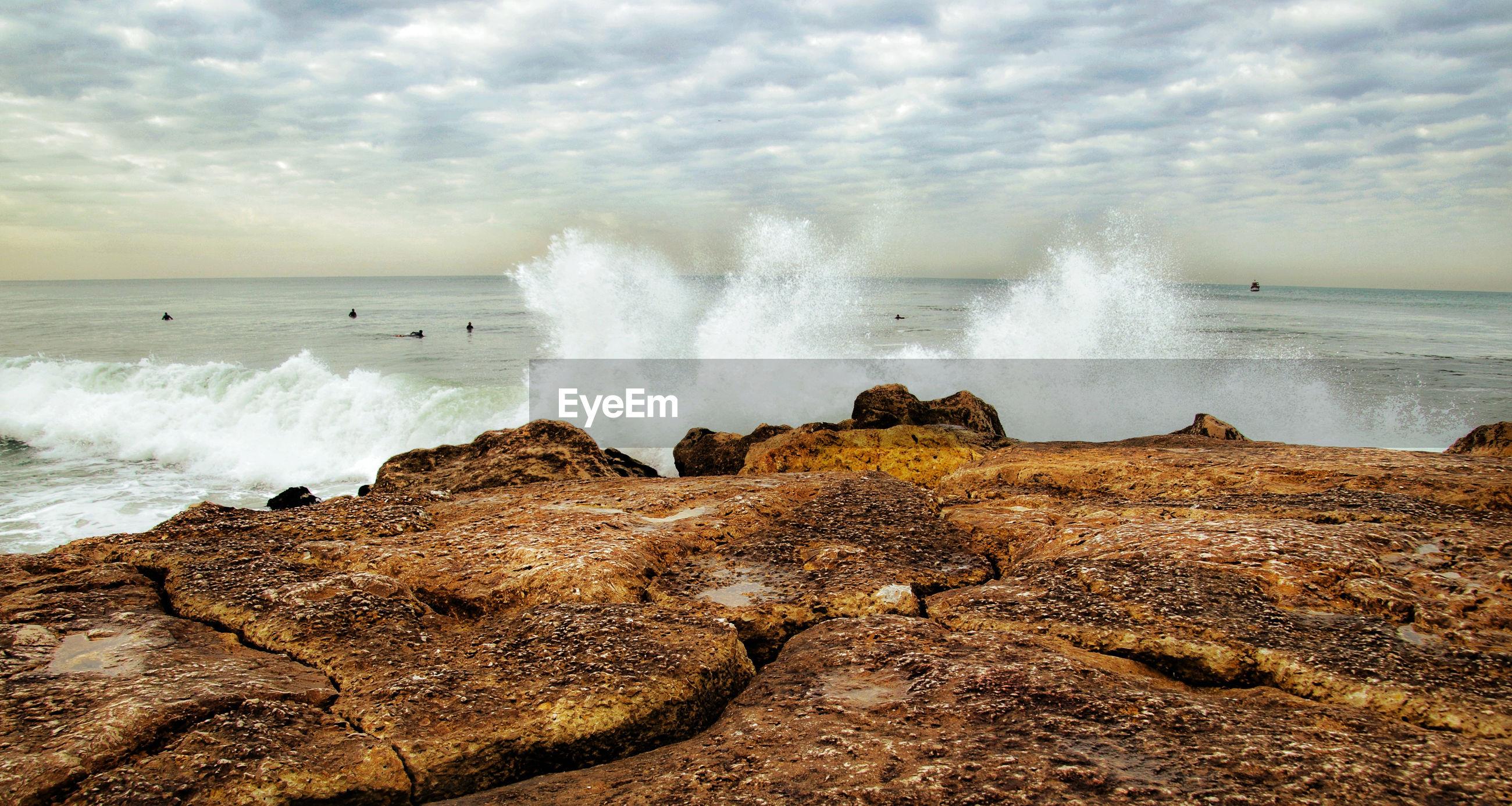 Panoramic shot of rocks on beach against sky