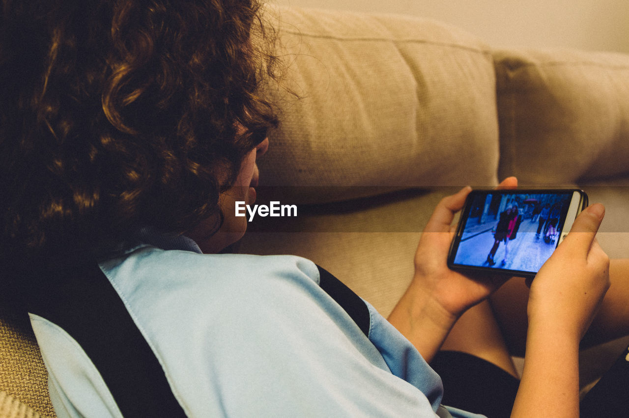 Girl Watching Photographs In Mobile Phone While Reclining On Sofa At Home