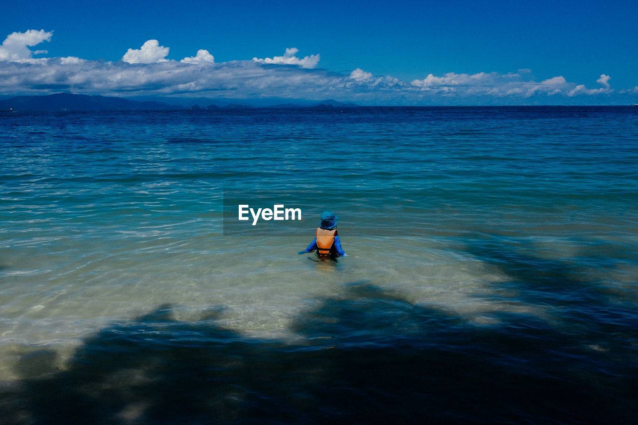 Rear View Of Person In Sea Against Sky