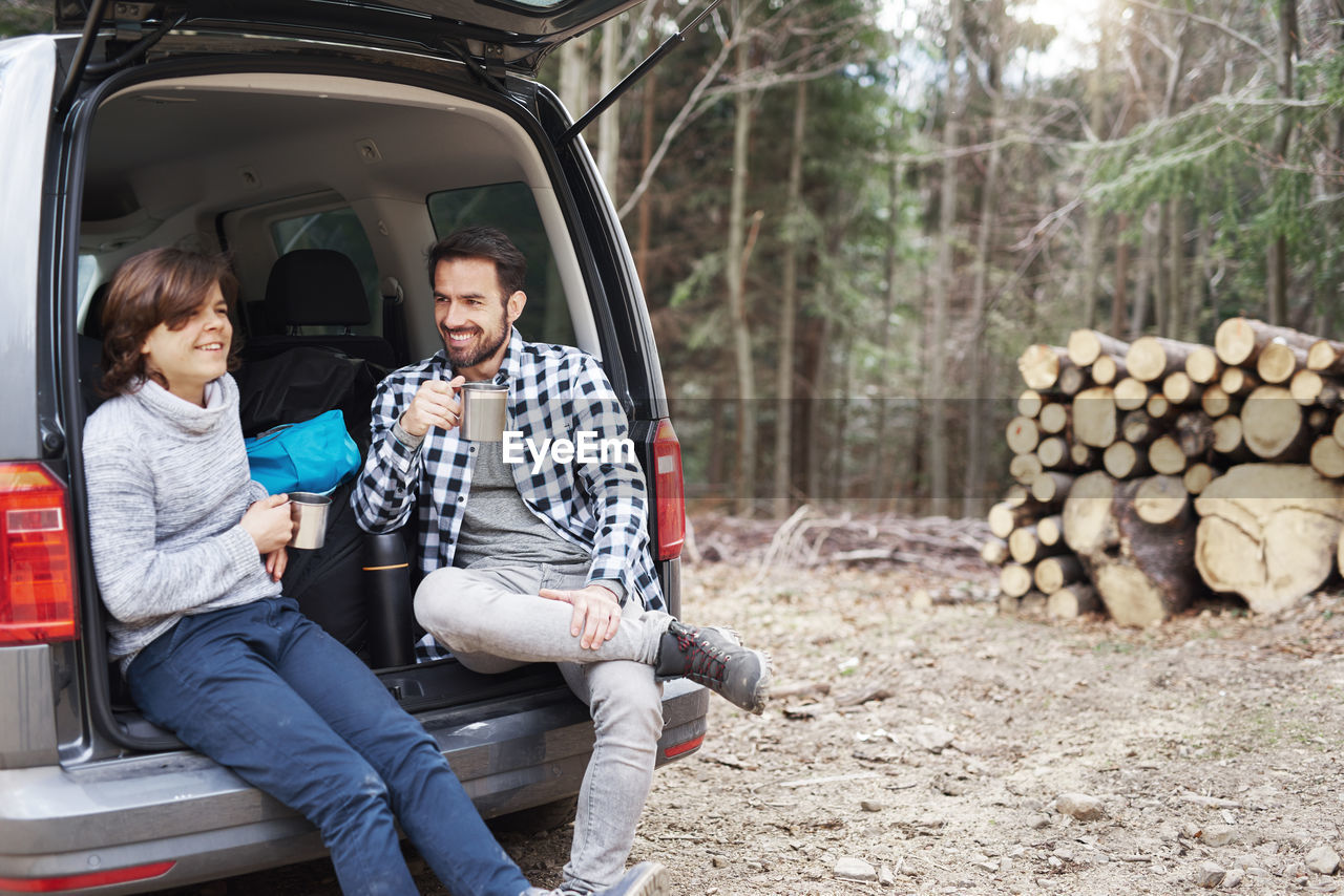 Father and son having coffee while sitting in car trunk during camping