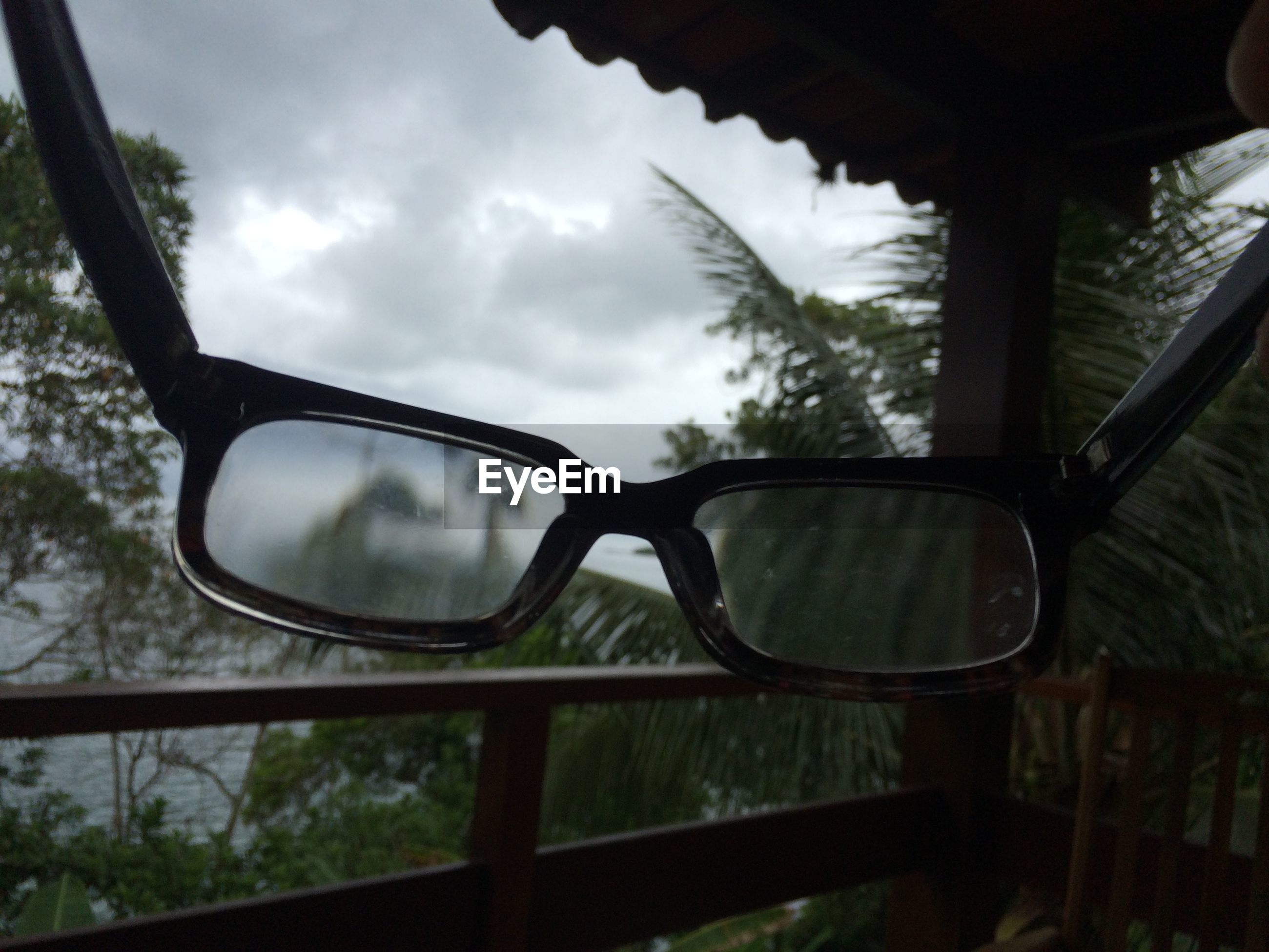 Close-up of eyeglasses at balcony against sky