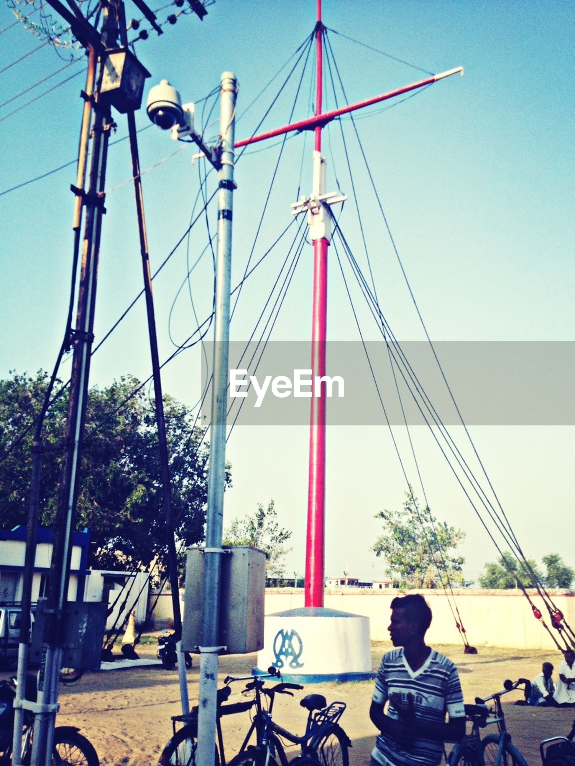 clear sky, transportation, mode of transport, men, bicycle, land vehicle, low angle view, electricity pylon, connection, leisure activity, blue, copy space, day, power line, lifestyles, outdoors, cable, sky