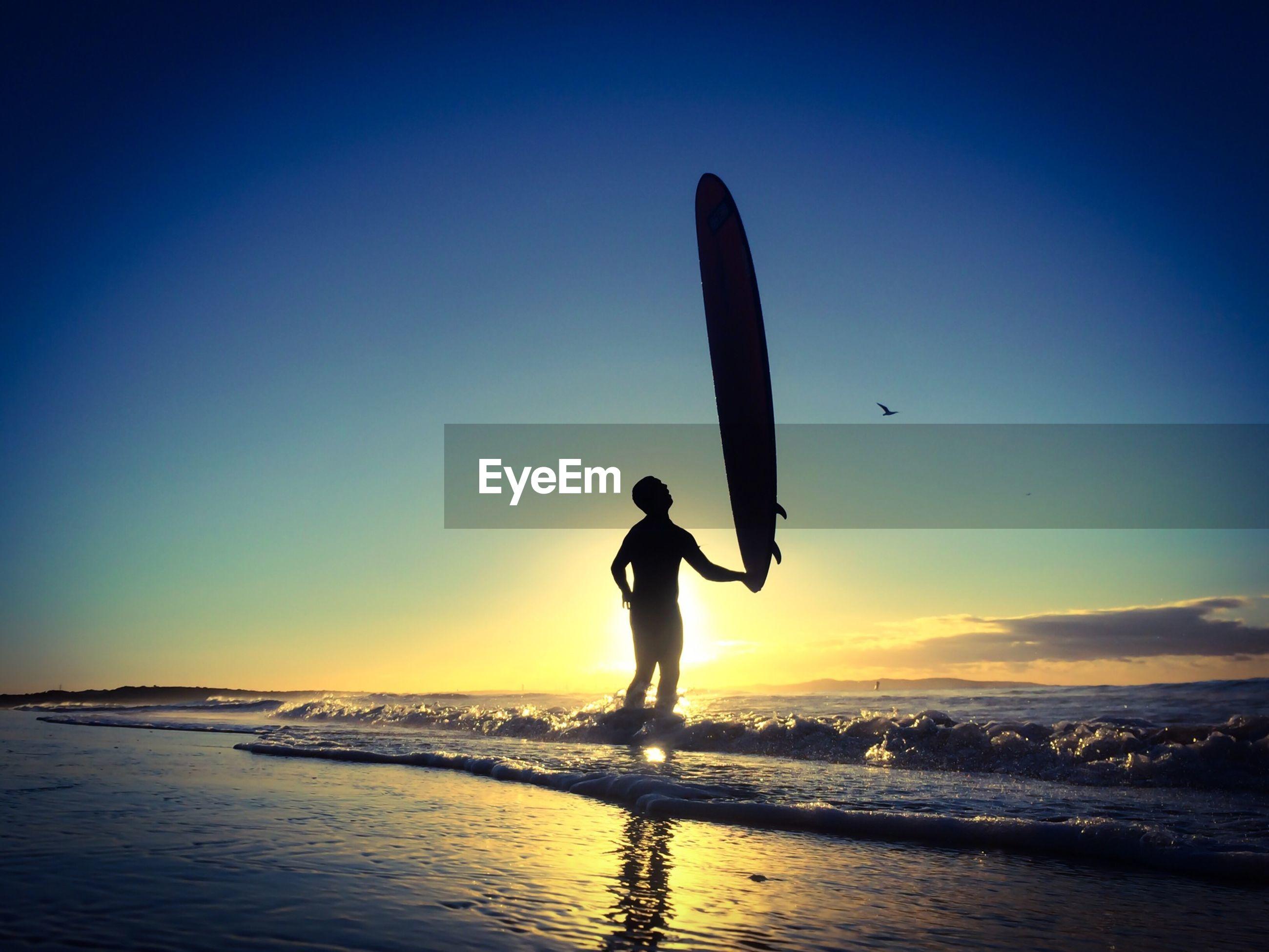 Silhouette man with surfboard on beach against clear blue sky
