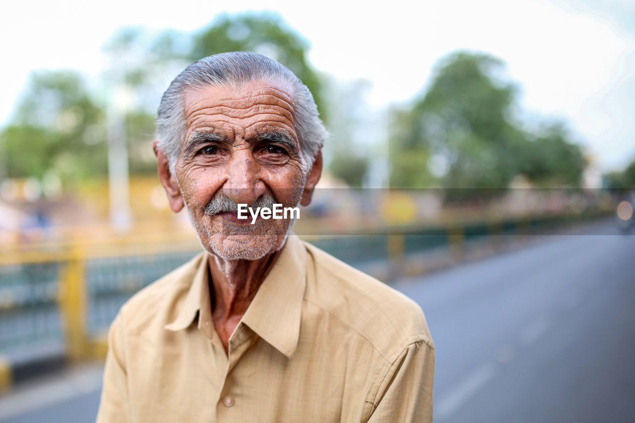 Portrait Of Senior Man Standing On Road Against Sky