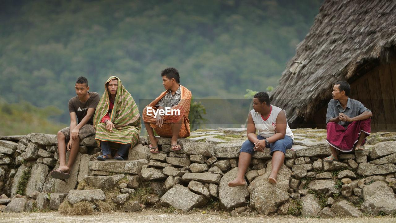 PEOPLE SITTING ON ROCKS