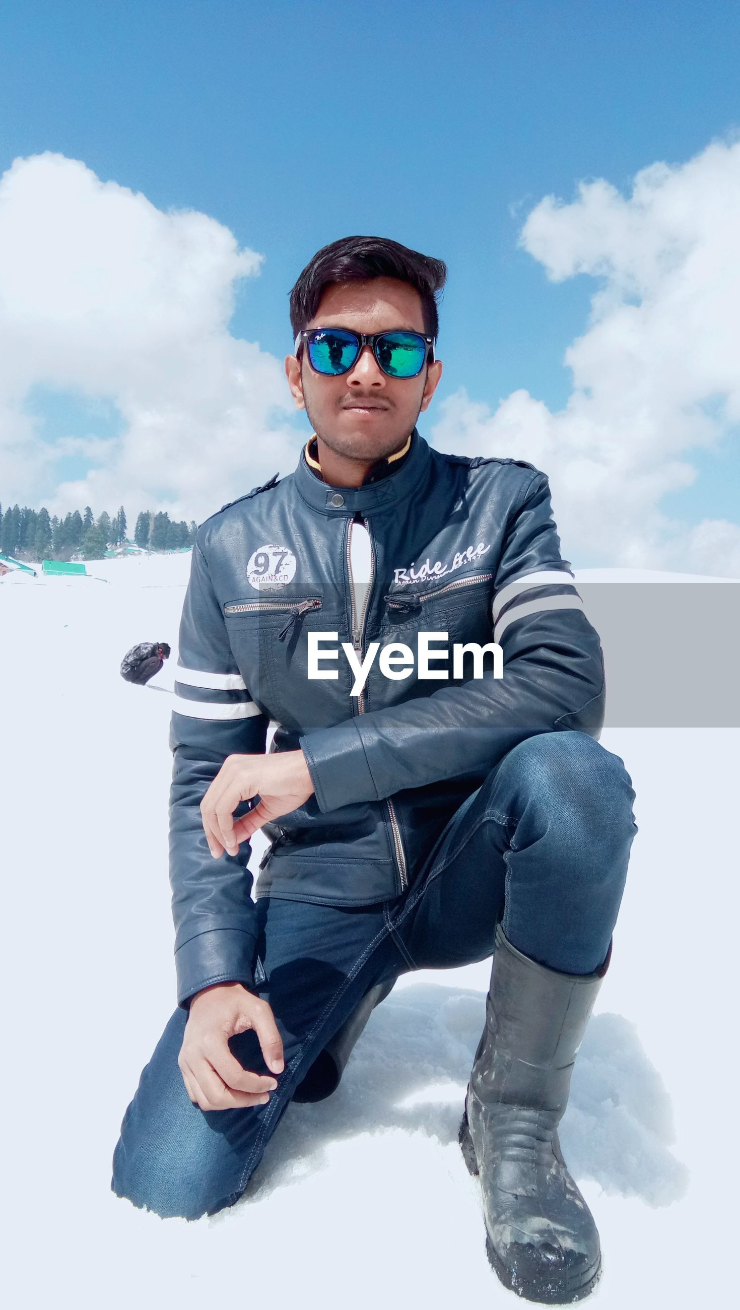 Portrait of young man wearing sunglasses crouching on snow covered land against sky