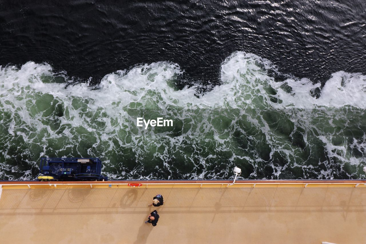 Directly Above View Of People Walking On Ferry Deck In Sea