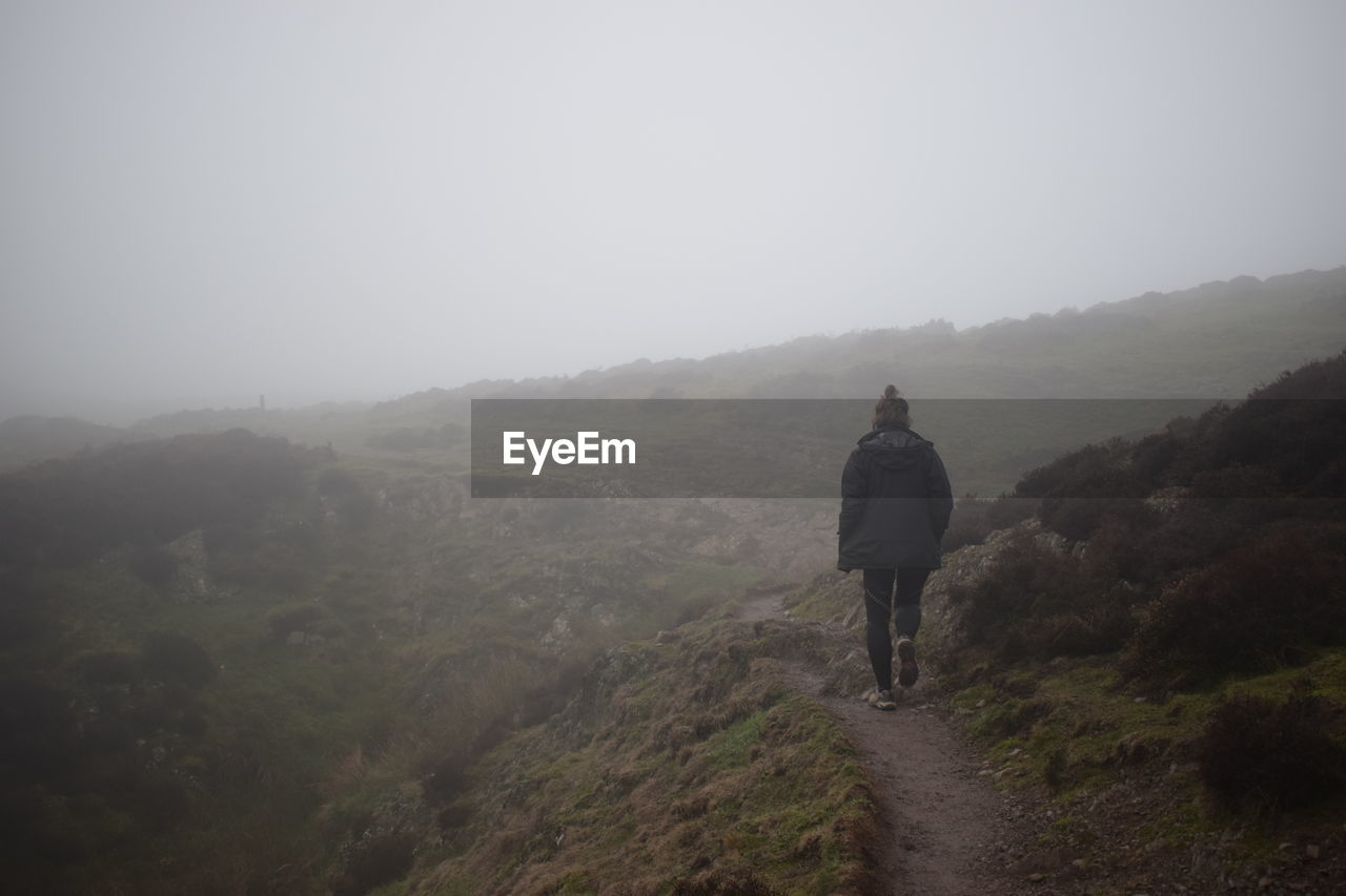 fog, rear view, one person, mountain, leisure activity, real people, full length, non-urban scene, lifestyles, sky, scenics - nature, beauty in nature, nature, tranquility, walking, tranquil scene, hiking, plant, outdoors
