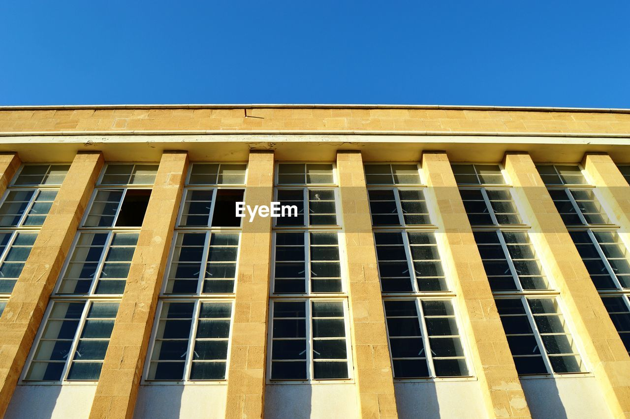 built structure, low angle view, architecture, building exterior, sky, clear sky, window, blue, no people, building, copy space, in a row, nature, sunlight, day, pattern, outdoors, repetition, side by side, modern