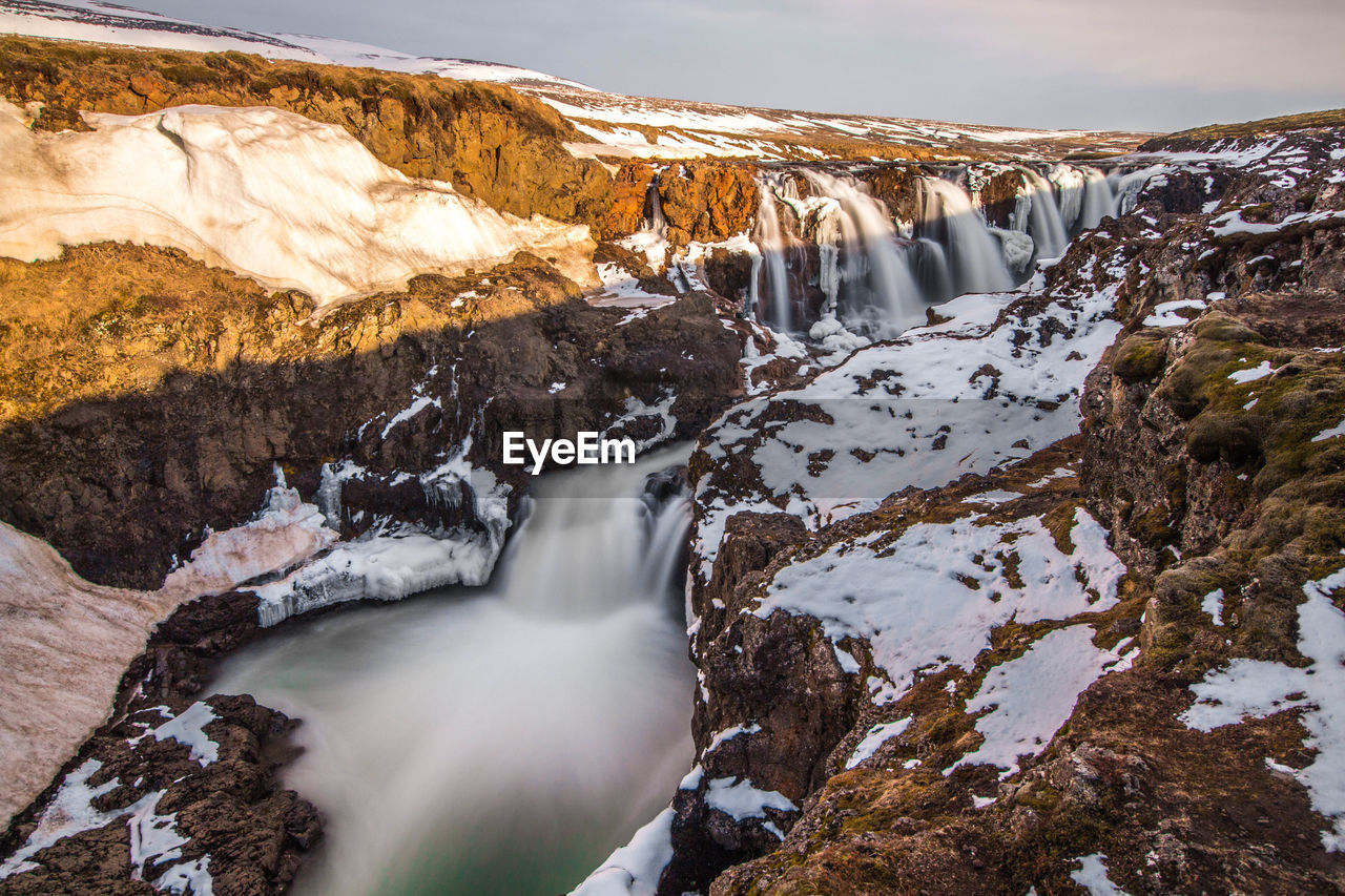 SCENIC VIEW OF WATERFALL AGAINST SNOW COVERED MOUNTAINS