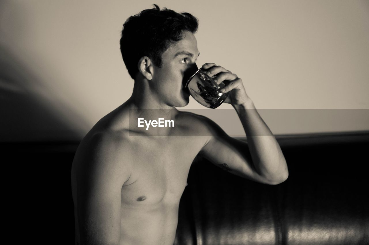 Shirtless Young Man Drinking Water At Home