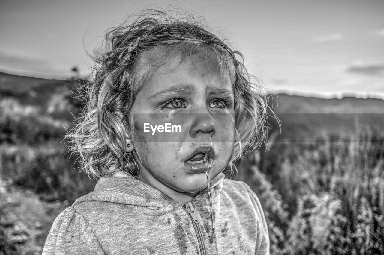Close-up of girl crying on field with runny nose