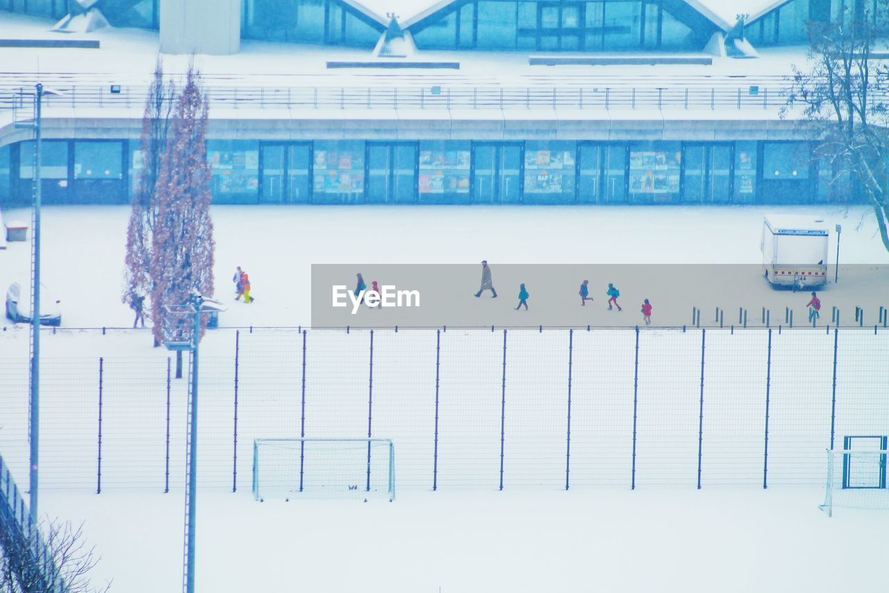 High angle view of people walking on snowcapped street