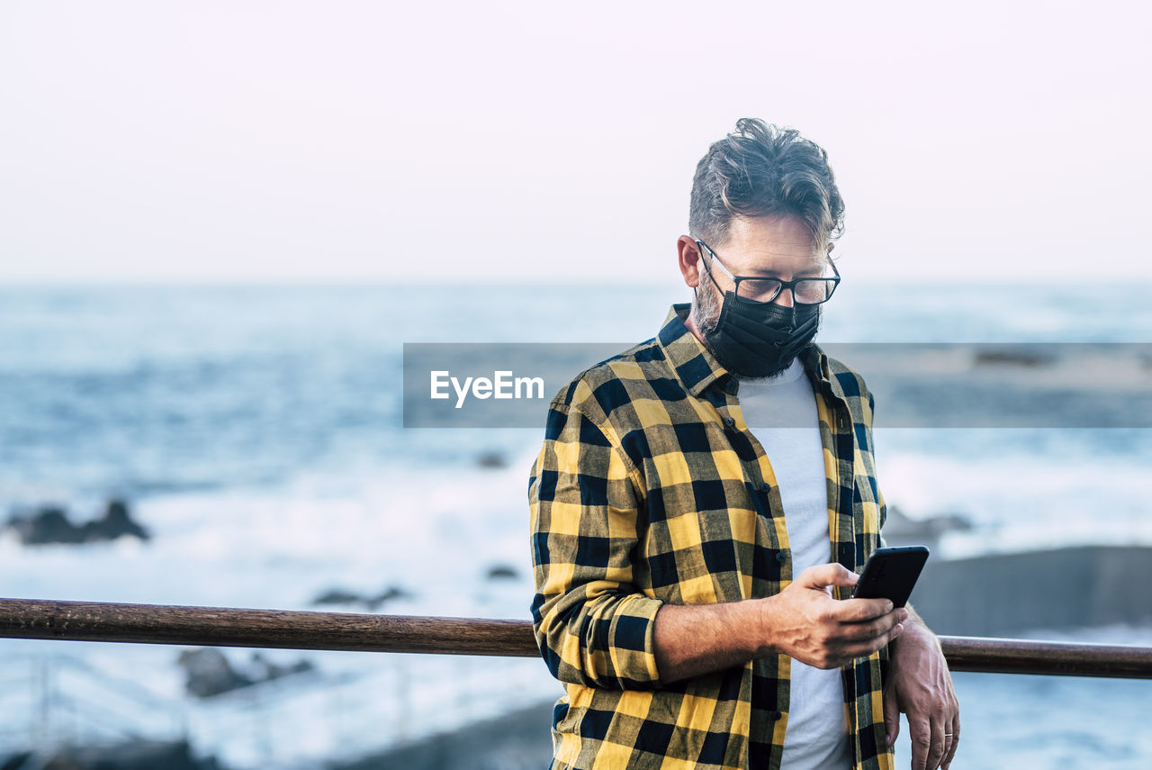 Mature man wearing mask using smart phone while standing against sea