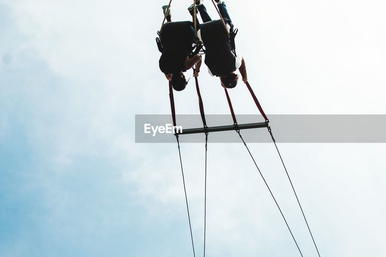 Low Angle View Of Men Enjoying On Amusement Park Ride Against Sky