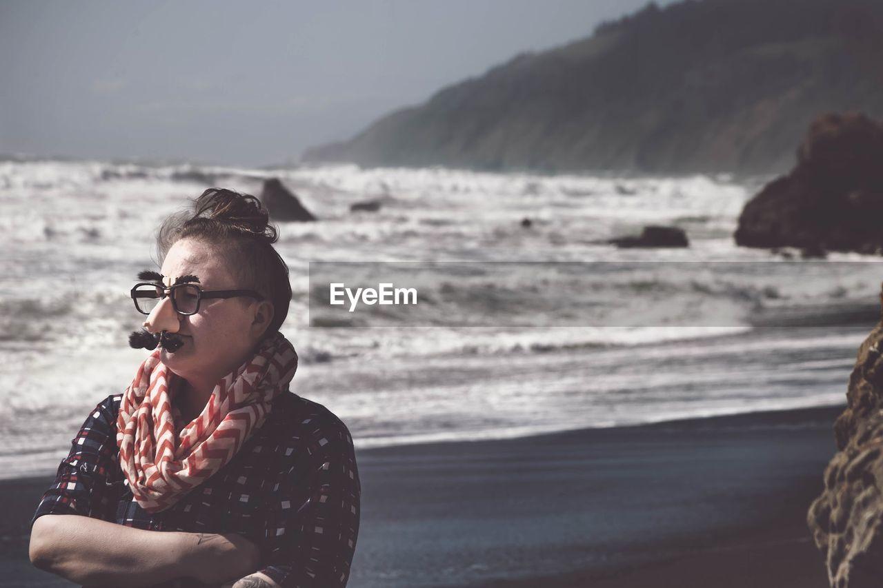 Woman Standing On Beach Wearing Mask