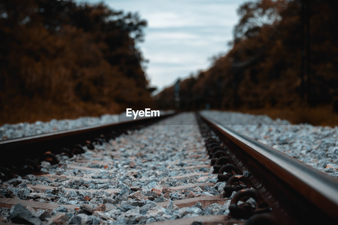 track, rail transportation, railroad track, transportation, no people, direction, metal, the way forward, sky, nature, mode of transportation, day, solid, selective focus, close-up, outdoors, surface level, diminishing perspective, gravel, rock, long