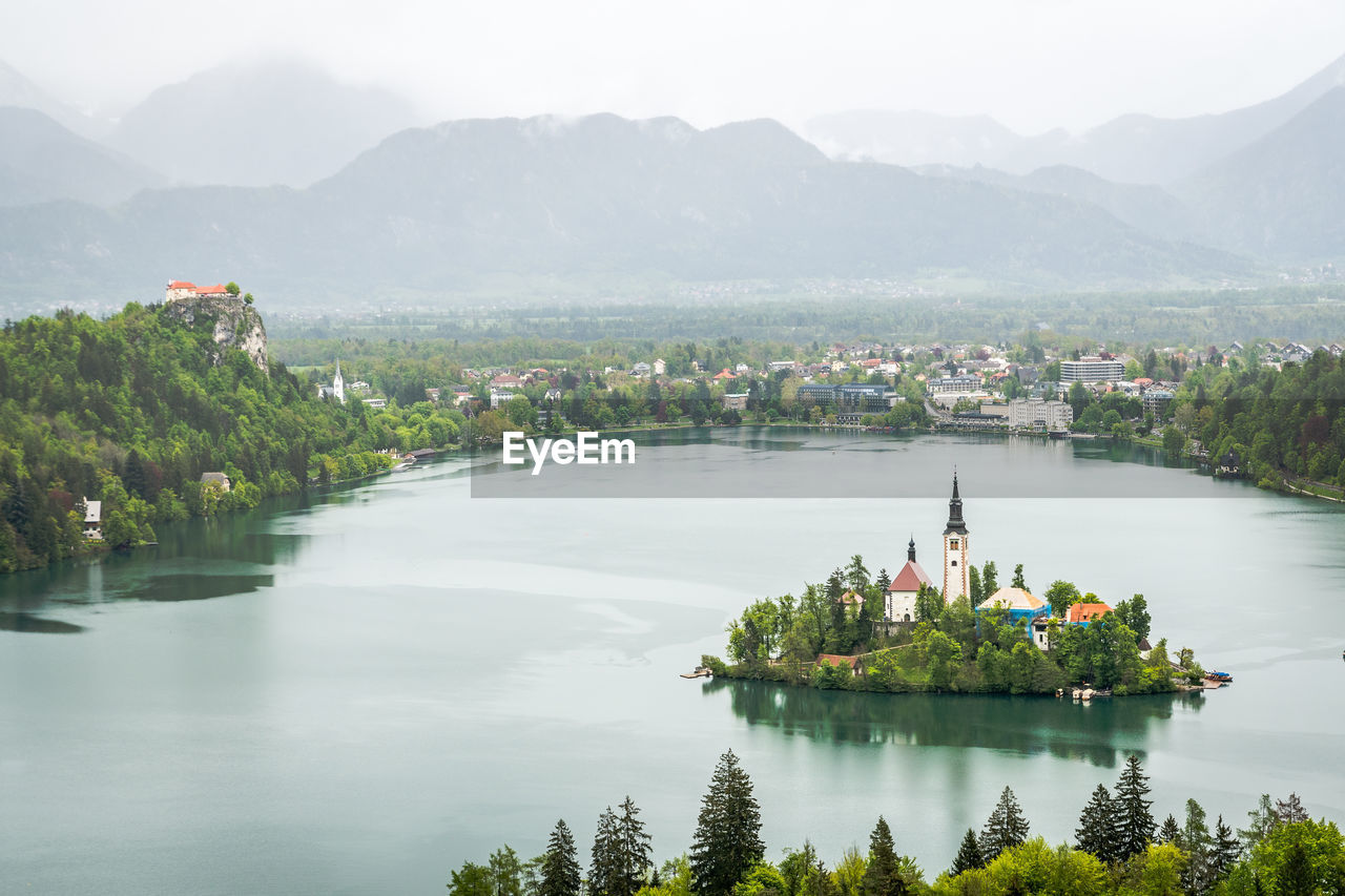 mountain, water, beauty in nature, scenics - nature, plant, architecture, nature, tree, built structure, lake, waterfront, tranquil scene, day, tranquility, building exterior, sky, mountain range, reflection, outdoors