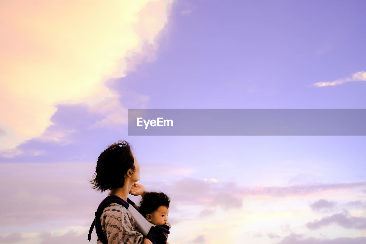 Woman Carrying Son Against Sky During Sunset