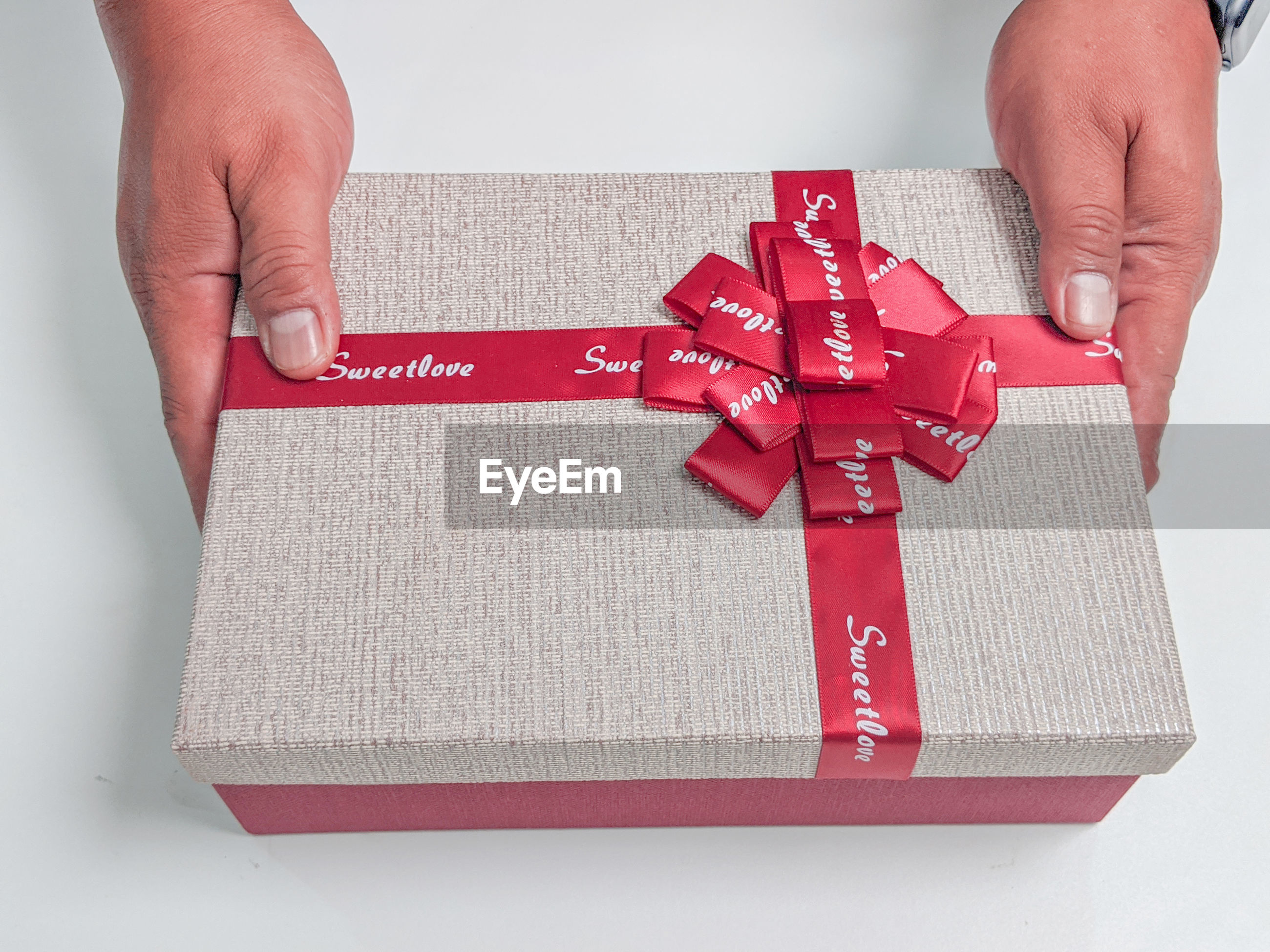 Cropped hands holding gift box on table