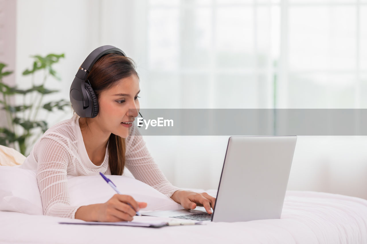 Young woman writing on notebook while video calling