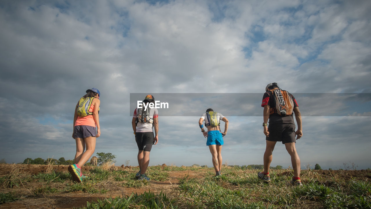 sky, cloud - sky, real people, nature, adventure, backpack, leisure activity, full length, standing, lifestyles, rear view, beauty in nature, walking, day, outdoors, men, hiking, togetherness, scenics, landscape, friendship, women, grass, people