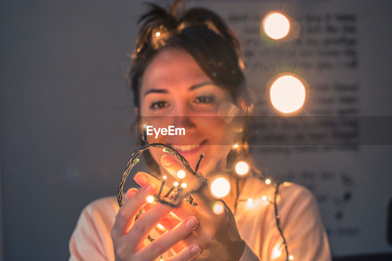 Smiling Woman Holding Illuminated Lights In Darkroom