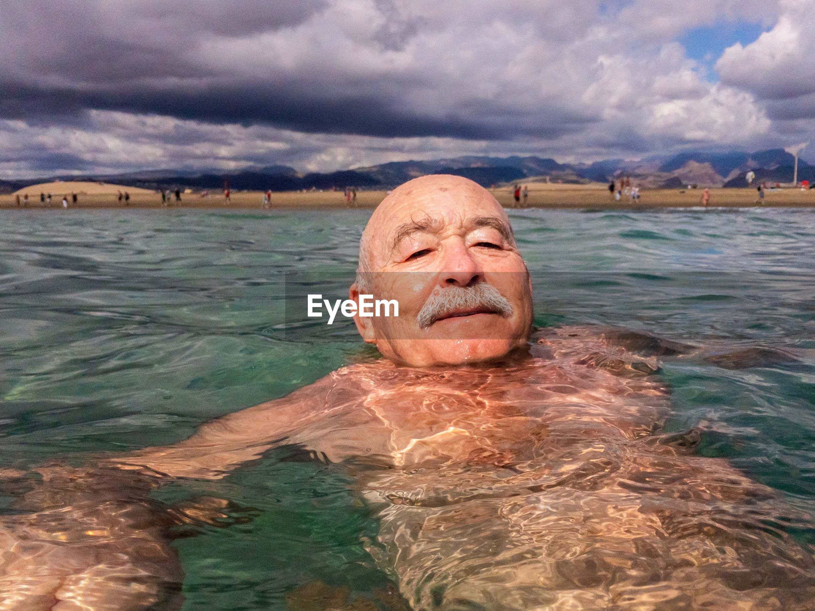Portrait of man swimming in sea against cloudy sky