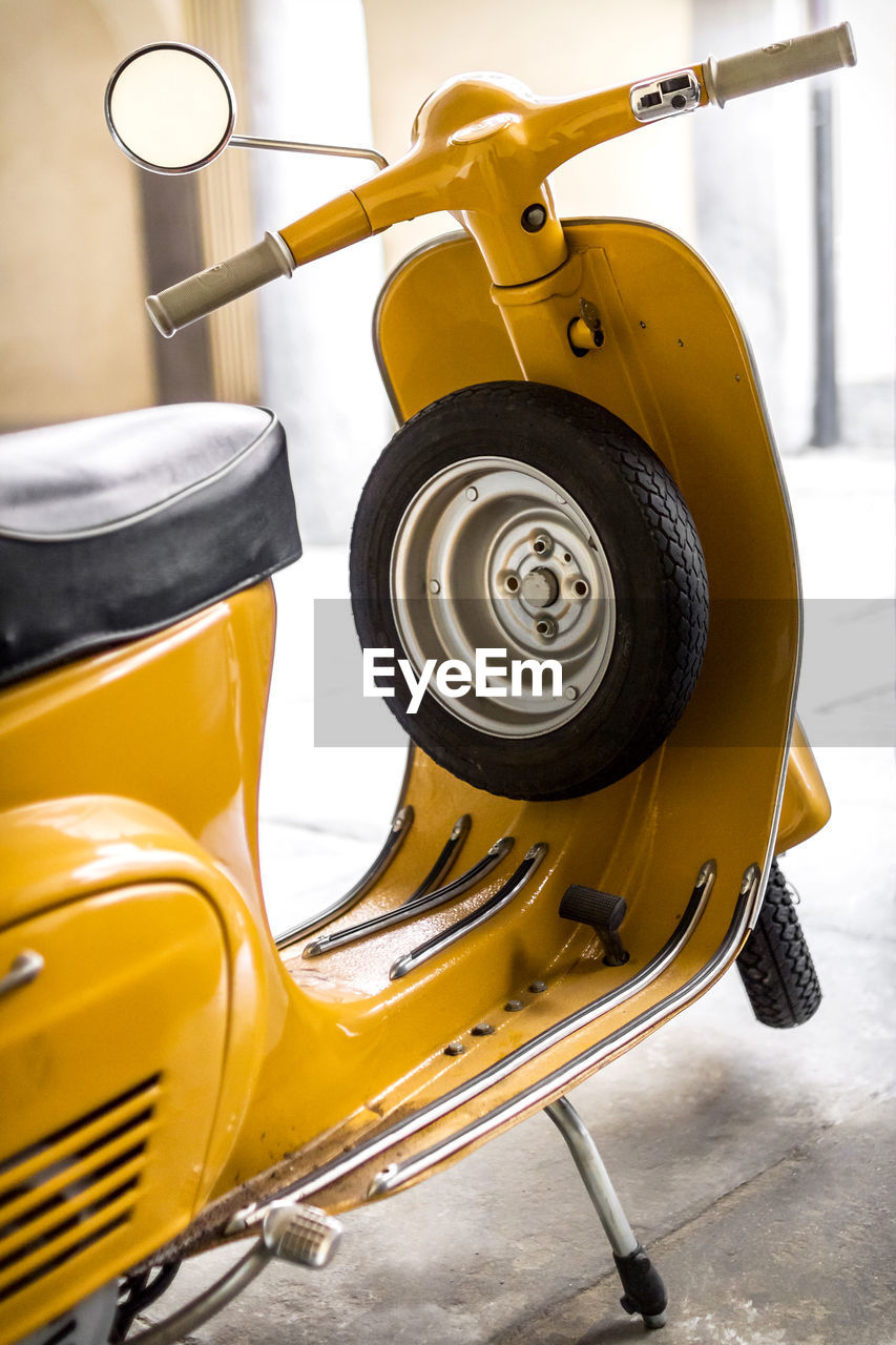 Parked yellow motor scooter with spare tire