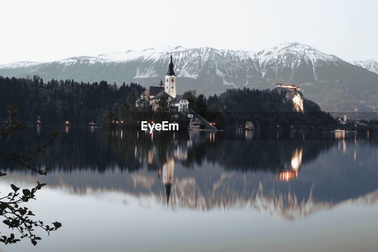 Church by lake against sky