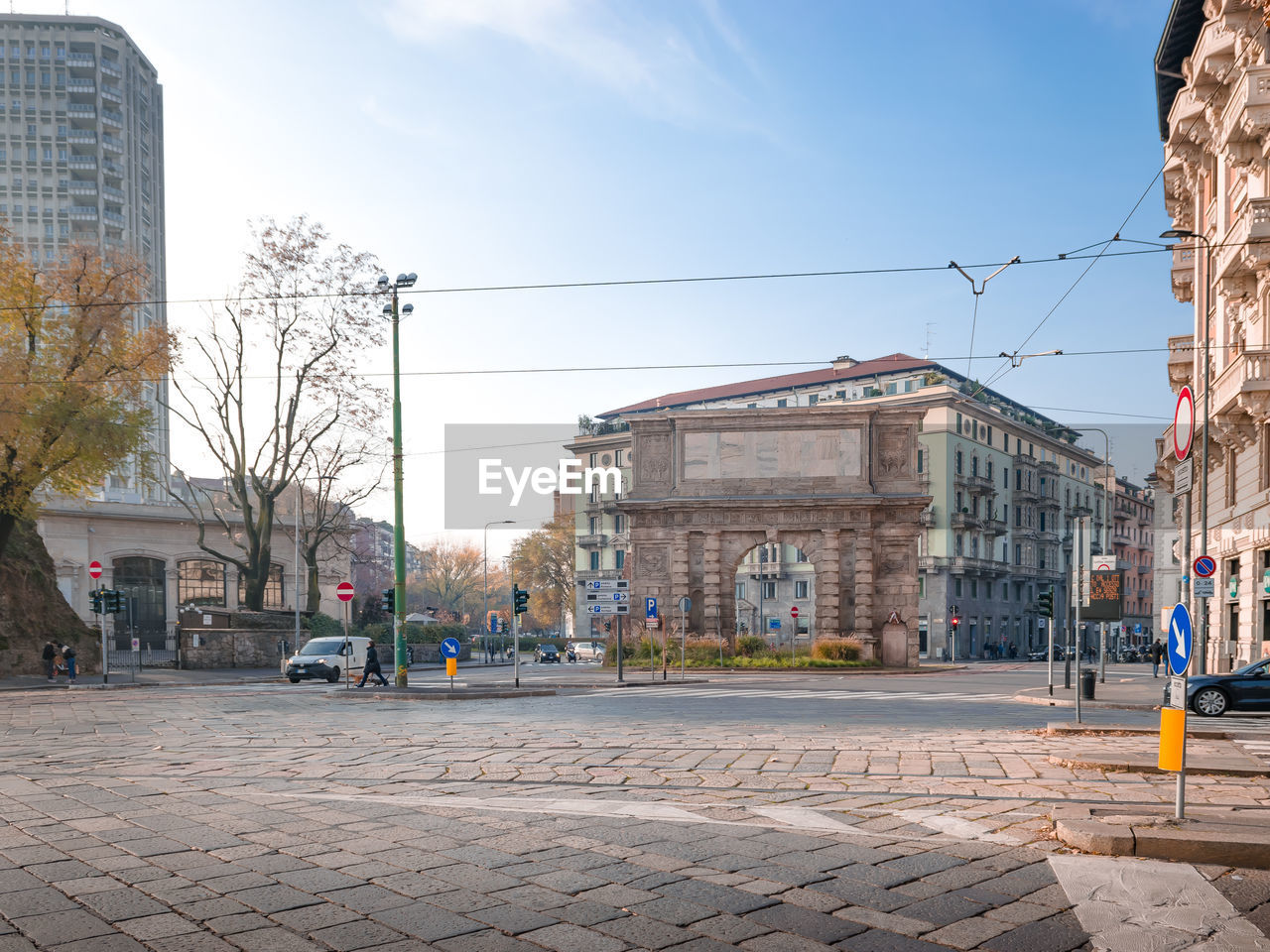 architecture, built structure, building exterior, city, sky, street, incidental people, building, nature, day, city life, transportation, outdoors, footpath, cobblestone, real people, city street, people, sunlight, road, paving stone