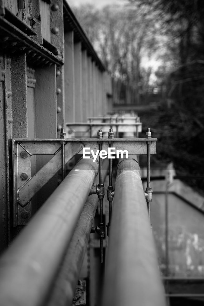 selective focus, architecture, pipe - tube, metal, built structure, pipeline, railing, no people, building exterior, outdoors, day, connection, nature, focus on background, pipe, transportation, fuel and power generation, close-up, rail transportation, track, power supply