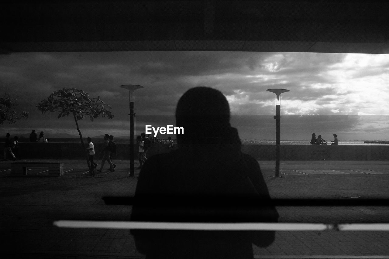 Silhouette person seen through glass window